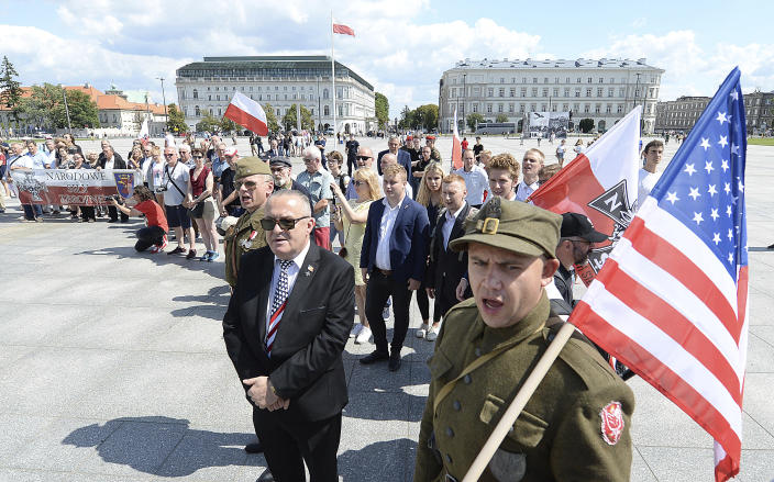 Polish officials and war veterans pay tribute to a World War II-era underground force that collaborated with Nazi German forces toward the end of the war in their battle against the Communists, who were imposing control on the nation, in Warsaw, Poland, Sunday, Aug. 11, 2019. President Andrzej Duda's official patronage and the presence of ruling party officials underlined the right-wing government's rehabilitation of a partisan unit that fought both Germans and Soviets and which is celebrated by the far right. (AP Photo/Czarek Sokolowski)