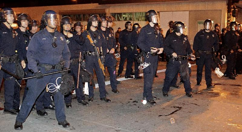 Oakland police are pelted with bottles and beverages as they prepare to clear Frank Ogawa Plaza of May Day protestors Tuesday, May 1, 2012 in Oakland, Calif. Hundreds of activists across the U.S. joined the worldwide May Day protests on Tuesday, with Occupy Wall Street members in several cities leading demonstrations and in some cases clashing with police. (AP Photo/Ben Margot)