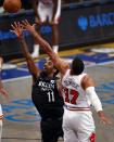 Brooklyn Nets guard Kyrie Irving (11) drives to the basket past Chicago Bulls forward Garrett Temple during the second half of an NBA basketball game Saturday, May 15, 2021, in New York. (AP Photo/Adam Hunger)