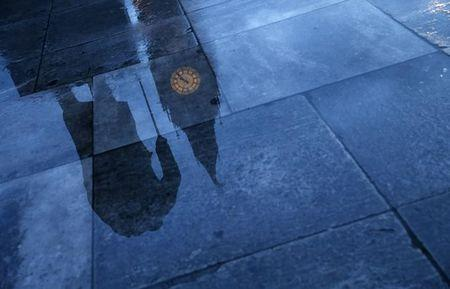 The statue of Britain's former Prime Minister Winston Churchill is reflected onto the rain covered pavement in front of the Houses of Parliament in London