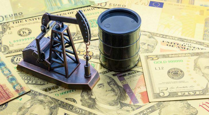 miniature oil barrel and oil well figures on top of stack of money