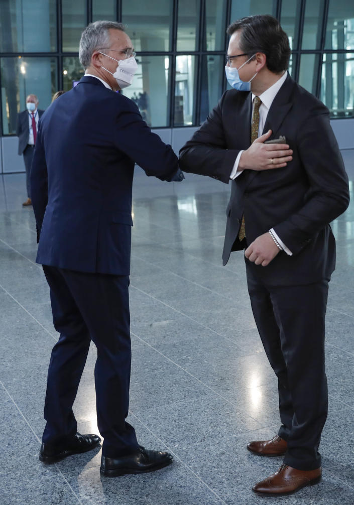 NATO Secretary General Jens Stoltenberg, left, greets Ukraine's Foreign Minister Dmytro Kuleba with an elbow bump prior to a meeting at NATO headquarters in Brussels, Tuesday, April 13, 2021. (AP Photo/Francisco Seco, Pool)