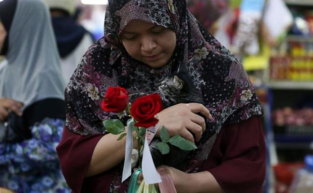 A vendor admires the stalk of rose she received at the Bayan Baru Market complex, Penang, in conjunction with International Womens Day, March 8, 2018.