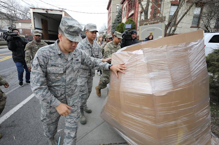 Members of the New York Air and Army National Guard move a pallet of bananas that was unloaded from a Feeding Westchester truck at the New Rochelle Community Action Partnership, at the WestCOP building in New Rochelle, March 12, 2020.