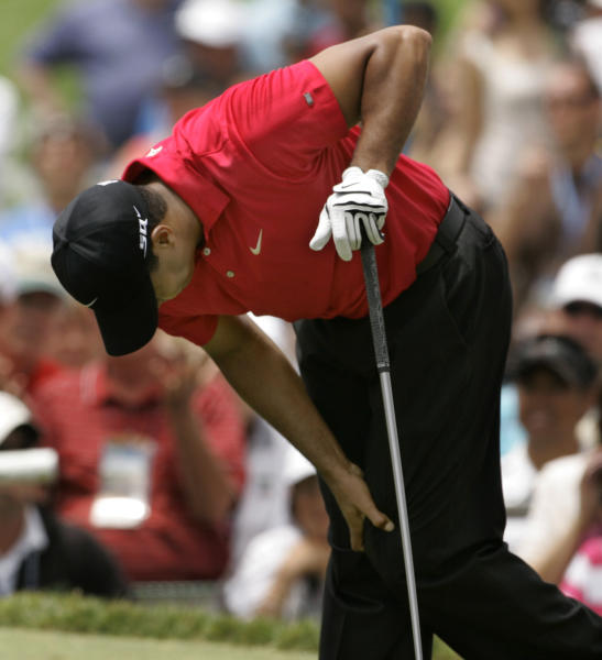 FILE - In this June 15, 2008, file photo, Tiger Woods holds onto his left knee after teeing off on the second hole during the fourth round of the US Open championship at Torrey Pines Golf Course in San Diego. He had a fourth back surgery with hopes of simply playing with his two children, not chasing Jack Nicklaus in history. (AP Photo/Charlie Riedel, File)
