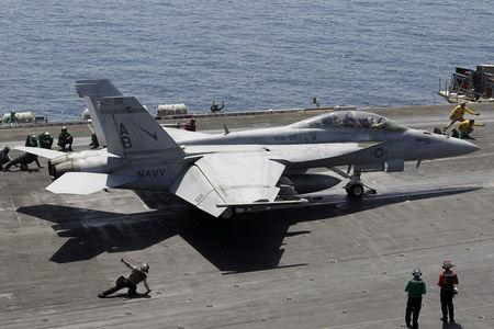 FILE PHOTO: A F/A-18E/F Super Hornets of Strike Fighter Attack Squadron 211 (VFA-211) is lined up for take off on the flight deck of the USS Theodore Roosevelt (CVN-71) aircraft carrier in the Gulf June 18, 2015. REUTERS/Hamad I Mohammed/File Photo