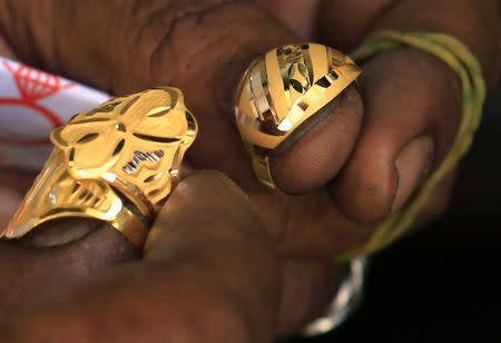 A blacksmith holds on to gold rings at the gold market in Omdurman