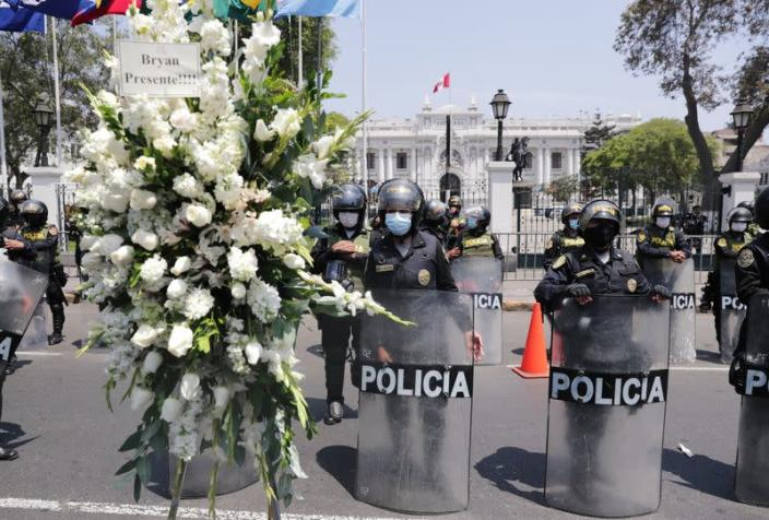 Police officers stand guard outside the government palace as people take to the streets and celebrate after interim President Manuel Merino resigned in a television address, in Lima