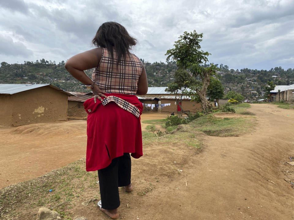"""Shekinah stands near her home in Beni, eastern Congo on Thursday, March 18, 2021. When she was working as a nurse's aide in northeastern Congo in January 2019, she said World Health Organization Dr. Boubacar Diallo, of Canada, offered her a job investigating Ebola cases at double her previous salary _ with a catch. """"When he asked me to sleep with him, given the financial difficulties of my family….I accepted."""" (AP Photo/Kudra Maliro)"""