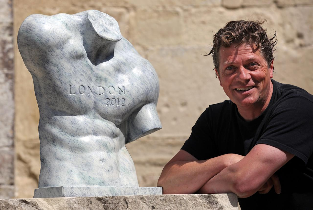 SALISBURY, ENGLAND - JUNE 18:  Sculpture Ben Dearnley poses for a photograph with a concept bronze of a 2012 Olympian that he has created in front of Salisbury Cathedral on June 18, 2012 in Salisbury, England. The sculptures - which focus on the 'power zones' of twelve of some of the UK's past and current Olympic and Paralympic champions - will be displayed at Salisbury Cathedral from June 23 until September 16 to coincide with the 2012 London Olympics and Paralympics.  (Photo by Matt Cardy/Getty Images)