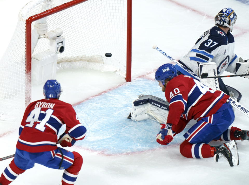 Montreal Canadiens' Joel Armia scores a short-handed goal past Winnipeg Jets goaltender Connor Hellebuyck as Canadiens' Paul Byron looks on during the second period of an NHL Stanley Cup playoff hockey game in Montreal, Sunday, June 6, 2021. (Paul Chiasson/The Canadian Press via AP)
