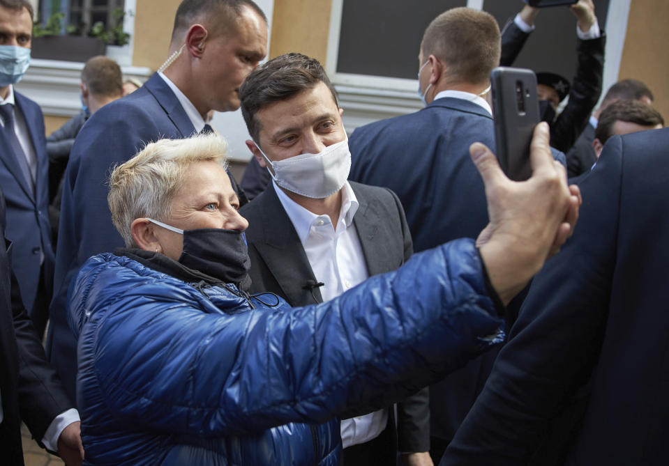 FILE In this file photo taken on Wednesday, June 3, 2020, A woman in a face mask to protect against coronavirus, takes a selfie with Ukrainian President Volodymyr Zelenskiy during his working visit in the town of Khmelnitsky, central Ukraine. Ukrainians are heading to the polls on Sunday, Oct. 25, 2020 to cast ballots in local elections seen as a key test for President Volodymyr Zelenskiy. Zelenskiy, a popular comedian without prior political experience, was elected by a landslide in April 2019 on promises to end fighting with Russia-backed separatists in eastern Ukraine, uproot endemic corruption and shore up a worsening economy. (Ukrainian Presidential Press Office via AP, File)
