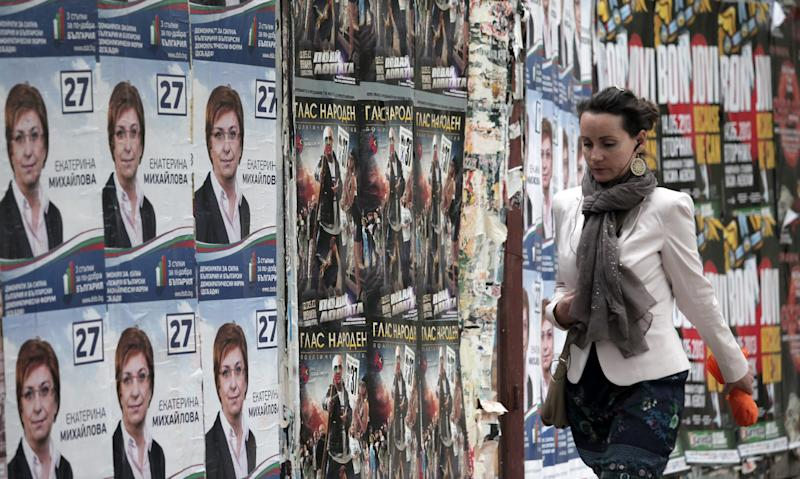 A woman passes by election campaign posters in Sofia, Thursday, May 9, 2013. A deeply fragmented Bulgaria heads into parliamentary elections Sunday, as frustration grows over the widening gap between once giddy hopes linked to EU membership and today's sobering reality. (AP Photo/Valentina Petrova)