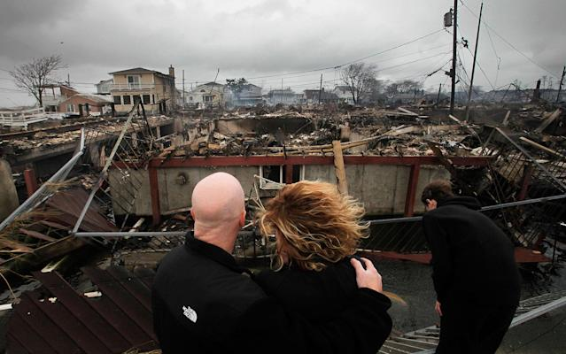 <p>Robert Connolly, left, embraces his wife Laura as they survey the remains of the home owned by her parents that burned to the ground in the Breezy Point section of New York, Tuesday, Oct. 30, 2012. More than 50 homes were destroyed in the fire which swept through the oceanfront community during superstorm Sandy. At right is their son, Kyle. (AP Photo/Mark Lennihan) </p>