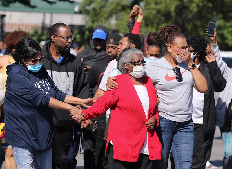 Odessa Riley, center in red sweater, was escorted by family members June 1 to the site where her son was fatally shot at 26th and Broadway in Louisville, Ky.