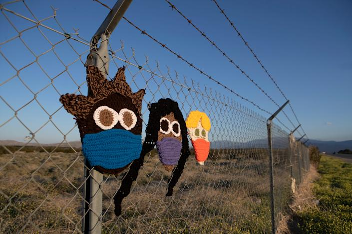"Knitted faces with masks are displayed on a fence along Palm Drive in Desert Hot Springs, Calif., on April 17, 2020. A Facebook post from the previous day had a photo of the yarn art with a longer banner that read, ""WE'LL RISE ABOVE THIS."""