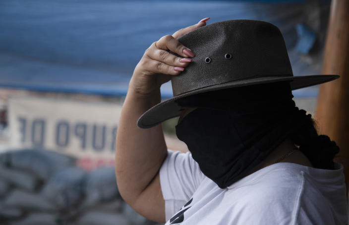 A masked woman who said she was displaced from her community by criminal groups adjusts her hat as she helps patrol a checkpoint run by a group of armed women who call themselves a self-defense group, at the entrance to El Terrero in Michoacan state, Mexico, Wednesday, Jan. 13, 2021. The rural area is traversed by dirt roads, through which they fear Jalisco gunmen could penetrate at a time when the homicide rate in Michoacán has spiked to levels not seen since 2013. (AP Photo/Armando Solis)