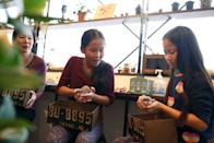 Anna (C), 11, and Yuna Cheung (R), 11, from Great Britain hold hedgehogs as their mother Kimberly Russel watches at the Harry hedgehog cafe in Tokyo, Japan, April 5, 2016. In a new animal-themed cafe, 20 to 30 hedgehogs of different breeds scrabble and snooze in glass tanks in Tokyo's Roppongi entertainment district. Customers have been queuing to play with the prickly mammals, which have long been sold in Japan as pets. The cafe's name Harry alludes to the Japanese word for hedgehog, harinezumi. REUTERS/Thomas Peter