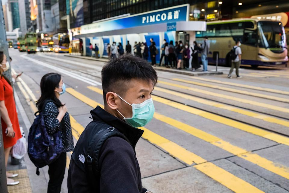 HONG KONG, CHINA - 2020/03/24: A masked man as a preventive measure crossing the street during the corona virus pandemic. As the coronavirus outbreak worsens, routine continues for businessmen and residents around the city, people wear face masks in fear of contracting the virus. (Photo by Willie Siau/SOPA Images/LightRocket via Getty Images)