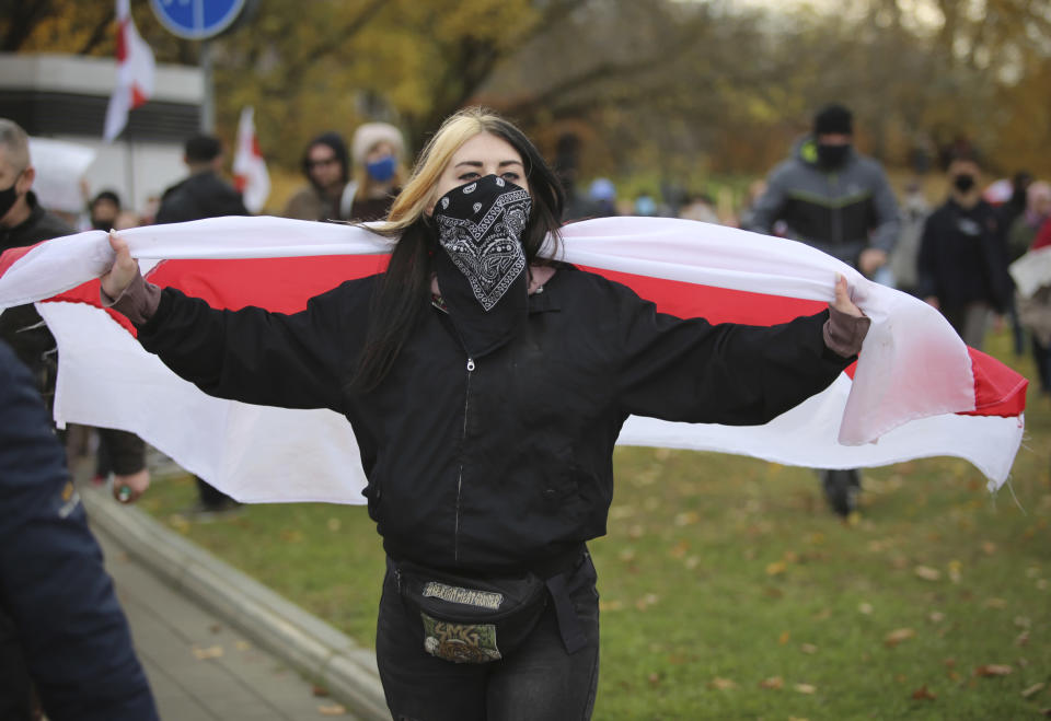 A woman holds an old Belarusian national flag during an opposition rally to protest the official presidential election results in Minsk, Belarus, Sunday, Nov. 1, 2020. Nearly three months after Belarus' authoritarian president's re-election to a sixth term in a vote widely seen as rigged, the continuing rallies have cast an unprecedented challenge to his 26-year rule. (AP Photo)