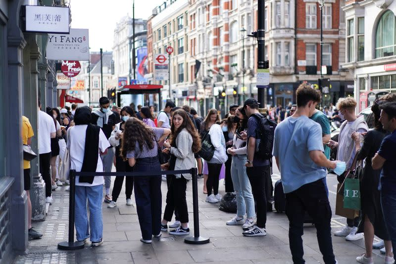 People gather outside a shop in the Chinatown area, amid the coronavirus disease (COVID-19) outbreak, in London
