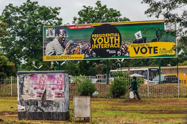 <p>A woman in military uniform walks past a billboard with a poster of ruling party Zimbabwe African National Union – Patriotic Front (Zanu PF) and a picture of President Robert Mugabe in Harare on Nov. 15, 2017. (Photo: AFP/Getty Images) </p>