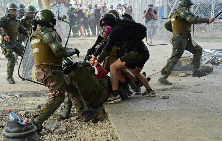 Demonstrators struggle with riot police during a protest in Santiago