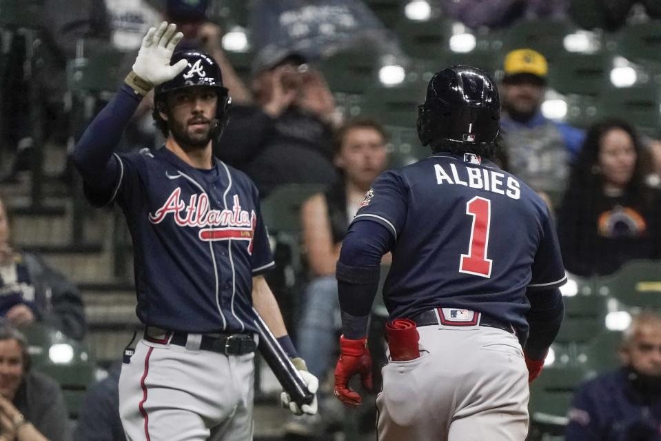 Atlanta Braves' Ozzie Albies is congratulated by Dansby Swanson after hitting a home run during the fifth inning of a baseball game against the Milwaukee Brewers Friday, May 14, 2021, in Milwaukee. (AP Photo/Morry Gash)