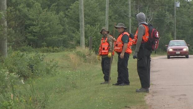 Three people in reflective vests help conduct the search for Jamie Sark, who was reported missing Wednesday on Lennox Island in western P.E.I. (Shane Hennessey/CBC - image credit)