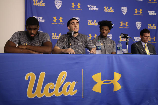 Flanked by Cody Riley, left, and Jalen Hill, third from left, UCLA basketball player LiAngelo Ball reads his statement as head coach Steve Alford listens during a news conference at UCLA Wednesday, Nov. 15, 2017, in Los Angeles. The three players were detained in Hangzhou following allegations of shoplifting last week before an NCAA college basketball game against Georgia Tech in Shanghai. (AP Photo/Jae C. Hong)