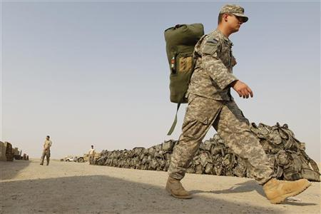 A U.S. soldier from the 1st Battalion,116th Infantry Regiment, carries his bag as he prepares to pull out from Iraq to Kuwait, at Tallil Air Base