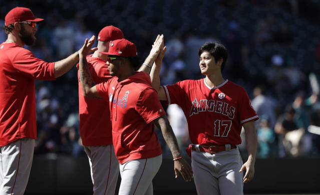 Los Angeles Angels' Shohei Ohtani (17) celebrates with teammates after they defeated the Seattle Mariners in a baseball game Sunday, July 21, 2019, in Seattle. (AP Photo/Elaine Thompson)