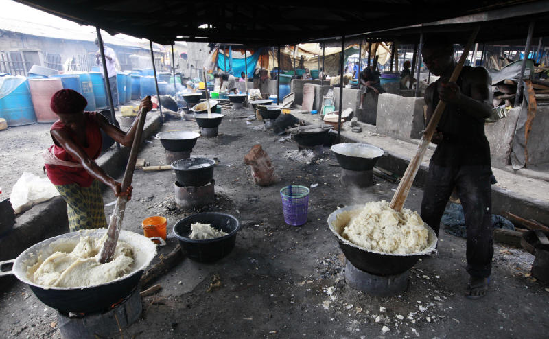 In this photo taken Friday, May 3, 2013, people prepare food made from cassava flour in a market in Lagos, Nigeria. Scientists say a disease destroying entire crops of cassava has spread out of East Africa into the heart of the continent, is attacking plants as far south as Angola and now threatens to move west into Nigeria, the world's biggest producer of the potato-like root that helps feed 500 million Africans. (AP Photo/Sunday Alamba)