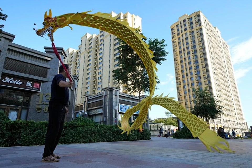A resident wields a cloth dragon outside the Evergrande Yujing Bay residential complex in Beijing, China (AP)