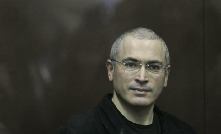 FILE - In this Thursday Dec. 30, 2010 file photo Mikhail Khodorkovsky looks from behind a glass enclosure in a court room in Moscow, Russia. President Vladimir Putin says he will pardon jailed oil tycoon Mikhail Khodorkovsky after more than a decade in prison. Putin told reporters after his marathon news conference Thursday Dec. 19, 2013, that Khodorkovsky submitted an appeal for pardon and he intends to grant it. (AP Photo/Alexander Zemlianichenko Jr, File)