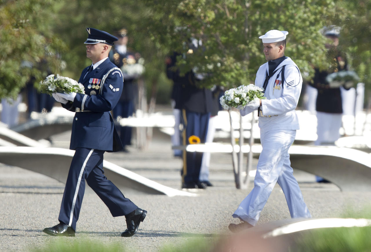 Service members carry flowers to each marker in the Pentagon memorial during a memorial service at the Pentagon September 11, 2011 in Arlington, Virginia.  Vice President Joseph R. Biden, Secretary of Defense Leon E. Panetta, Chairman of the Joint Chief of Staff Navy Admiral Mike Mullen and others will attend a memorial service at the Pentagon Memorial to commemorate the 10th anniversary the September 11, 2001 terrorist attacks on the United States.  (Photo by Brendan Smialowski/Getty Images)
