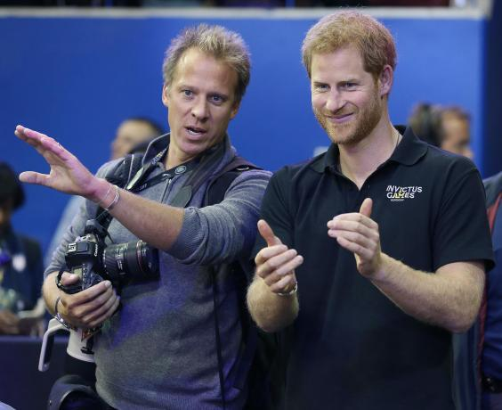 Royal photographer Chris Jackson goes over medal ceremony order with Prince Harry (Getty Images)