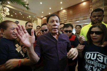 Rodrigo Duterte (C), a seven-term Philippine mayor, walks with his supporters during proclamation ceremony as a presidential candidate held at a hotel in Manila November 30, 2015. REUTERS/Romeo Ranoco/File Photo