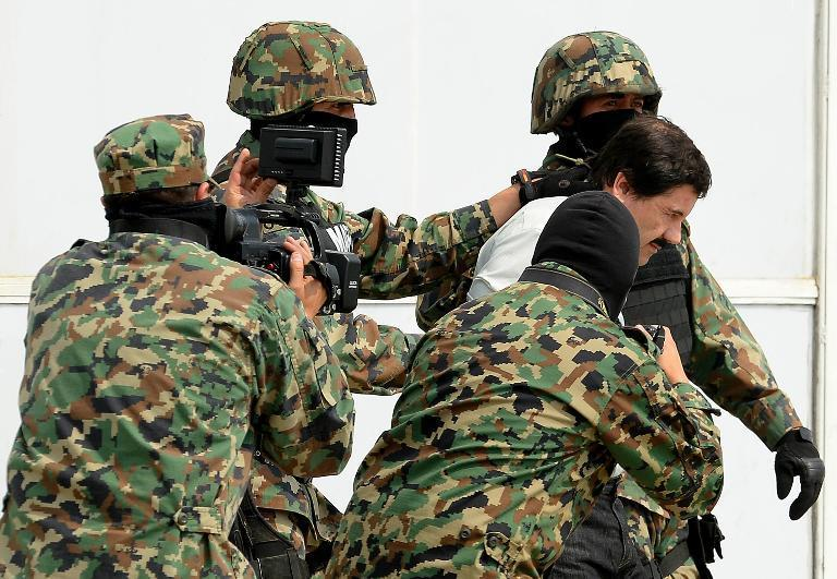 """Mexican drug trafficker Joaquin Guzman Loera aka """"el Chapo Guzman"""", is escorted by marines as he is presented to the press on February 22, 2014 in Mexico City"""