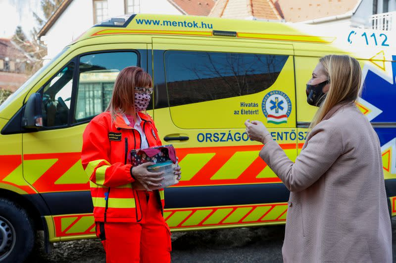 Eszter Harmath talks with a paramedic as she delivers pastries, during COVID-19 pandemic, in Szentendre