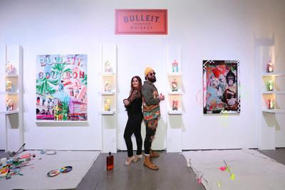 Artists Elidea and Jason Skeldon in front of limited-edition Bulleit Art in a Bottle Collection and accompanying canvases.
