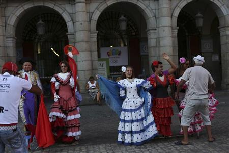 Tourists have their photo taken as they pose with flamenco dresses next to a sign that shows Madrid's 2020 Olympics candidate city logo at Madrid's Plaza Mayor square