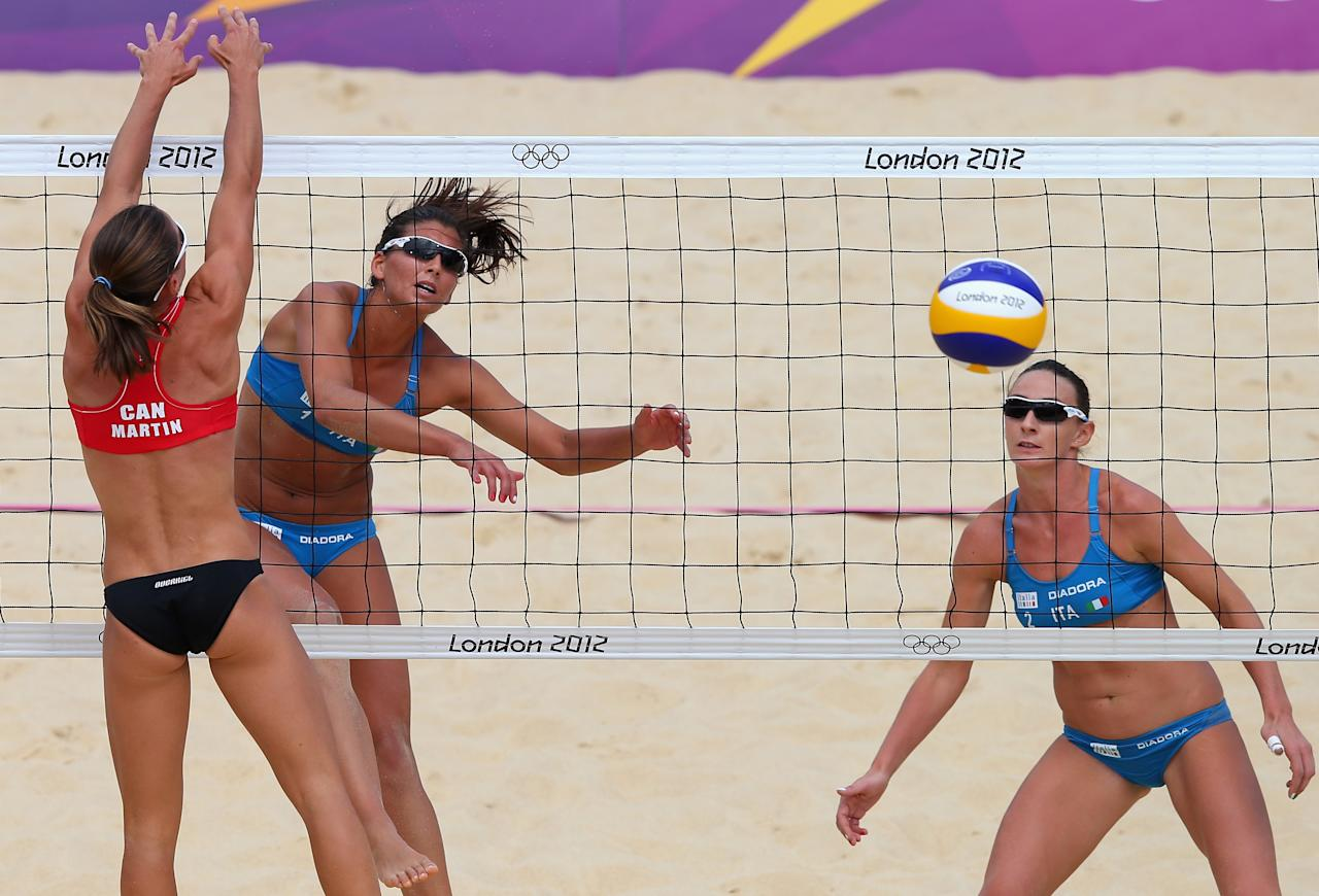 LONDON, ENGLAND - AUGUST 02:  Marta Menegatti of Italy hits a shot past Annie Martin of Canada  during the Women's Beach Volleyball preliminary match between Canada and Italy on Day 6 of the London 2012 Olympic Games at Horse Guards Parade on August 2, 2012 in London, England.  (Photo by Ryan Pierse/Getty Images)
