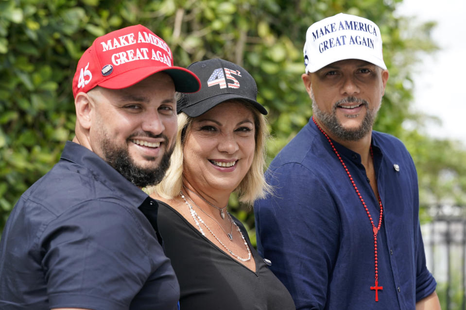 Tirso Luis, left, Ana Paez, and German Pinelli, right, members of the band Los 3 de la Habana, pose for a photograph, Thursday, Oct. 22, 2020, in Miami. The Cuban artists, who sought asylum in the U.S., have composed a salsa song in support of President Donald Trump, which is now being used as a full-fledged campaign ad. (AP Photo/Lynne Sladky)