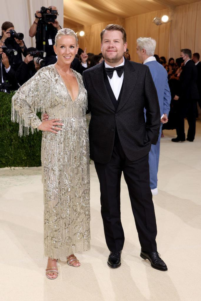 Julia Carey wears a long sparkly long sleeve gown with fringe and James Corden wears a dark suit