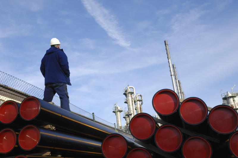 A person in a hard hat standing near a stack of pipelines.