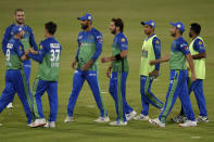 Multan Sultans spinner Shahid Afridi, center, celebrates with teammates after taking the wicket of Lahore Qalandars batsman Mohammad Hafeez during the second eliminator cricket match of Pakistan Super League T20 cup at National Stadium in Karachi, Pakistan, Sunday, Nov. 15, 2020. (AP Photo/Fareed Khan)