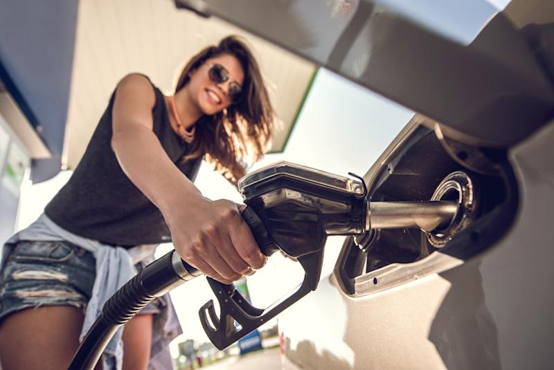 Close up of a woman refueling her car at fuel pump.