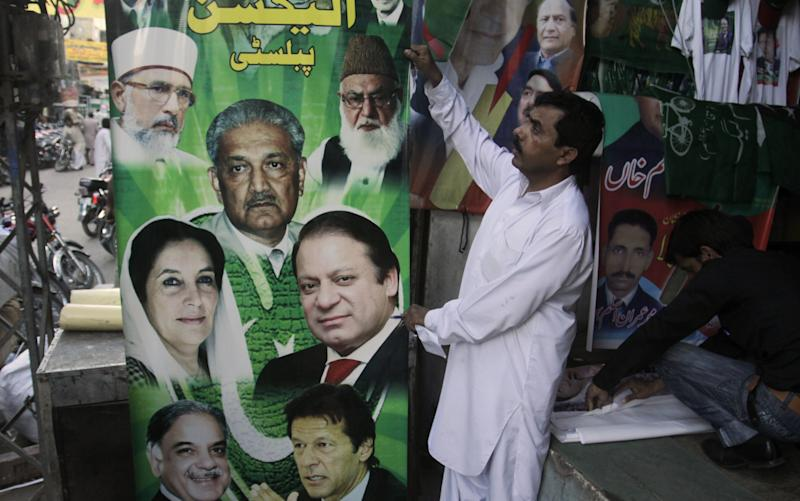 Pakistani vendors fix posters of candidates taking part in the upcoming parliamentary elections in Lahore, Pakistan on Friday, April 5, 2013. Pakistani officials have provoked both laughter and criticism in recent days as they vetted potential candidates in the country's upcoming national elections with questions that veered between the controversial and the bizarre. (AP Photo/K.M. Chaudary)