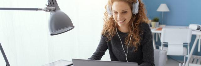 Young woman wearing headphones taking online class.